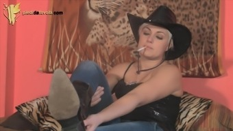 Smoking cowgirl shows some pantyhose underneath her jeans